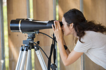 Woman looking through binoculars on tripod