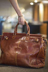 Close-up of a woman's hand picking up a leather purse