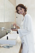 Woman mixing hair dye in a bathroom