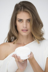 Portrait of a woman holding a container of moisturizer cream