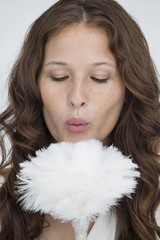 Woman blowing on a feather duster