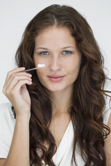 Portrait of a woman applying moisturizer cream on her face