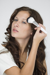Woman doing make-up with a make-up brush