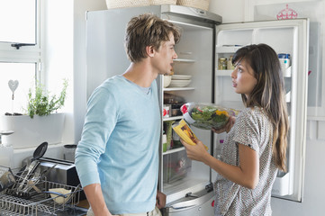 Couple talking in front of a refrigerator in the kitchen