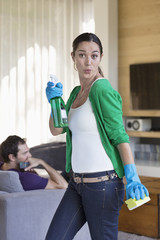 Woman holding cleaning equipment with her husband sitting on a couch