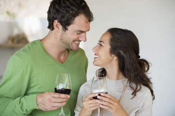 Couple holding wine glasses and smiling