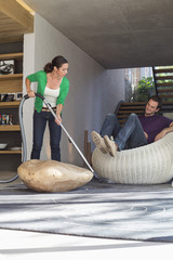 Woman cleaning house with a vacuum cleaner with her husband sitting on a seat