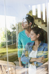 Couple standing behind a glass wall