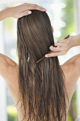 Rear view of a woman combing her hair