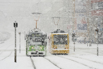 Winter city with trams and snow