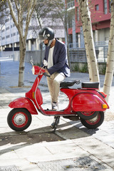 Man standing with a scooter