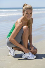 Smiling woman tying her shoelaces on the beach