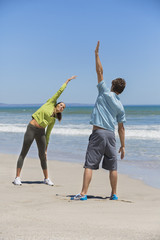 Woman and her coach exercising on the beach