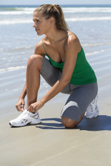 Woman tying her shoelaces on the beach