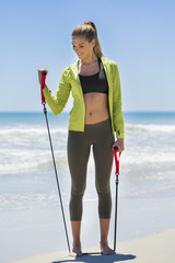 Woman exercise with a chest expander on the beach