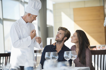 Chef talking to couple at restaurant