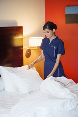 Maid making a bed in a hotel room