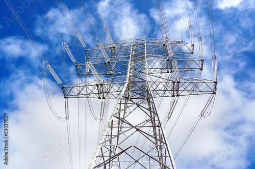 High voltage transmission tower against blue sky