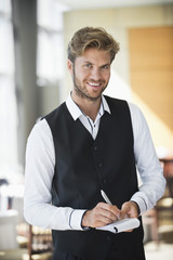 Portrait of a waiter taking order in a restaurant