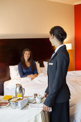 Waitress serving food to a woman in a hotel room