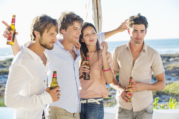 Group of friends enjoying beer outdoors on vacation