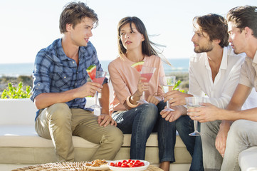 Group of friends enjoying drinks outdoors on vacation