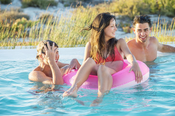 Three friends enjoying in a swimming pool on the beach