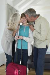 Grandparents kissing their grandson at home