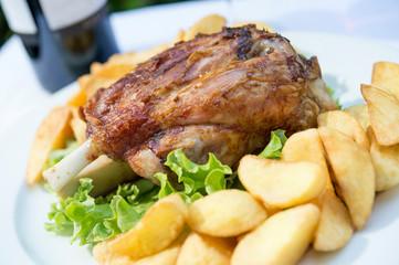 Stinco di maiale con patatine al forno e insalata