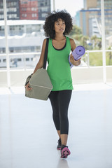 Woman carrying an exercise mat and a bag