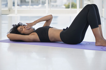 Woman lying on an exercise mat and yawning
