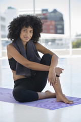 Smiling woman sitting on an exercise mat