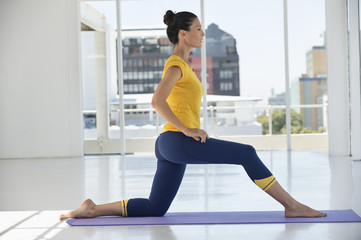 Woman exercising on exercise mat in a gym