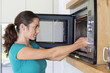 Woman putting food into a oven