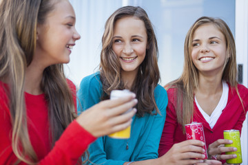 Close-up of three girls holding soft drink cans