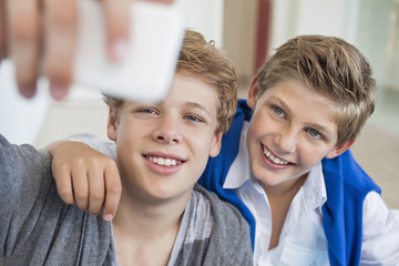 Two teenage boys taking a picture of themselves with a mobile phone