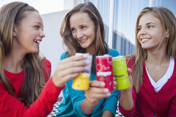 Close-up of three girls toasting with soft drink cans