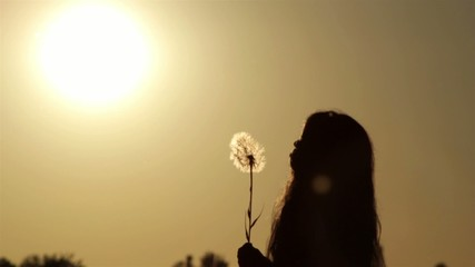 silhouette of a girl at sunset with a dandelion flower