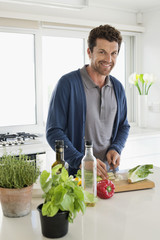Man chopping vegetables in a kitchen