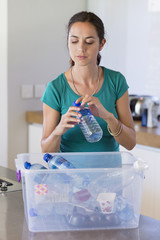 Woman putting a bottle in a recycling bin