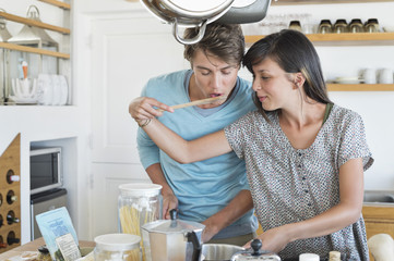 Woman tasting food to her husband in the kitchen