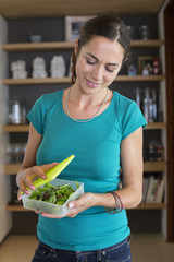 Woman holding leaf vegetables in a container and smiling at home