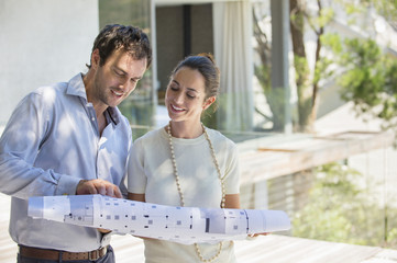 Couple looking at blueprint and smiling