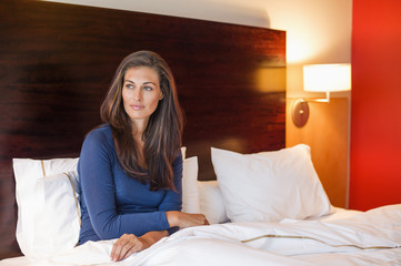Woman sitting on the bed in a hotel room