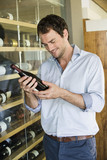 Smiling man looking at a wine bottle