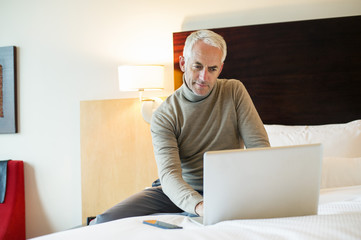 Man using a laptop in a hotel room
