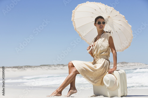 Beautiful woman sitting on a suitcase with an umbrella on the beach