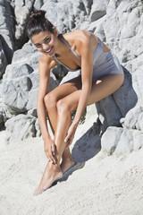 Beautiful woman applying suntan lotion on her leg