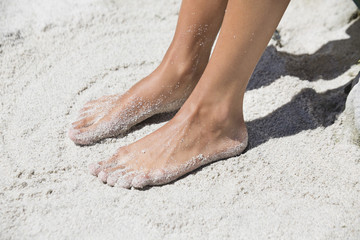 Woman's feet in sand on the beach
