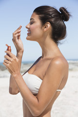 Beautiful woman smelling suntan lotion on the beach